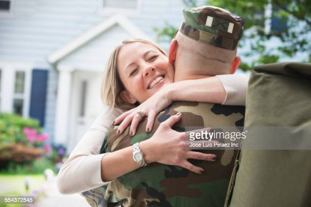 caucasian returning soldier hugging wife - military spouse stock pictures, royalty-free photos & images