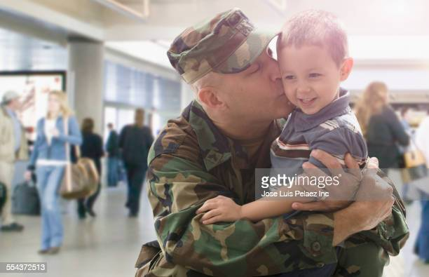 Caucasian returning soldier kissing son in airport