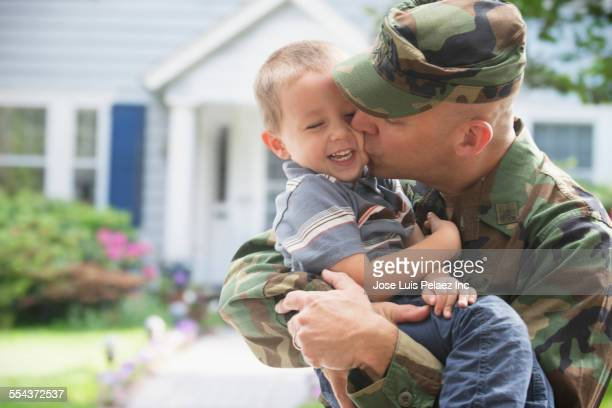 Caucasian returning soldier kissing son