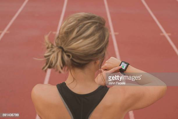 Caucasian runner checking watch on sports field