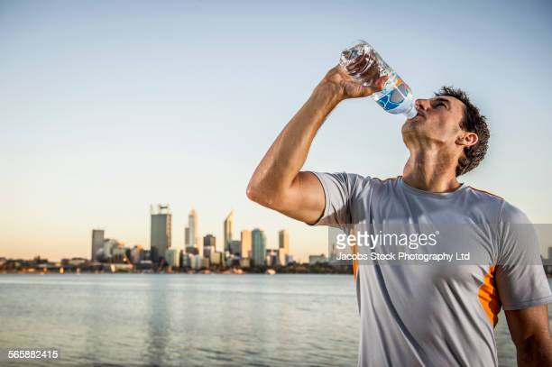 Caucasian runner drinking water bottle near urban waterfront, Perth, Western Australia, Australia