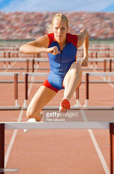 caucasian runner jumping over hurdles on track - hurdling stock photos and pictures