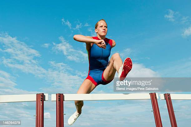 caucasian runner jumping over hurdles on track - hurdling track event stock pictures, royalty-free photos & images