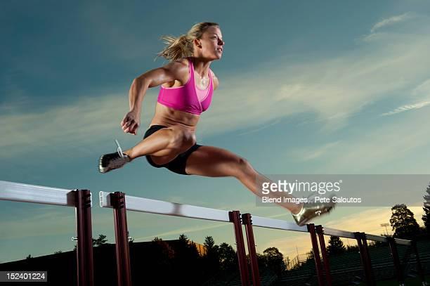 Caucasian runner jumping over hurdles