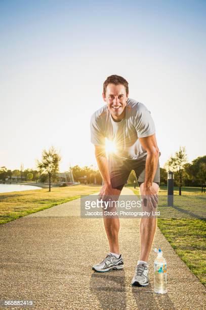 Caucasian runner resting on concrete path in park