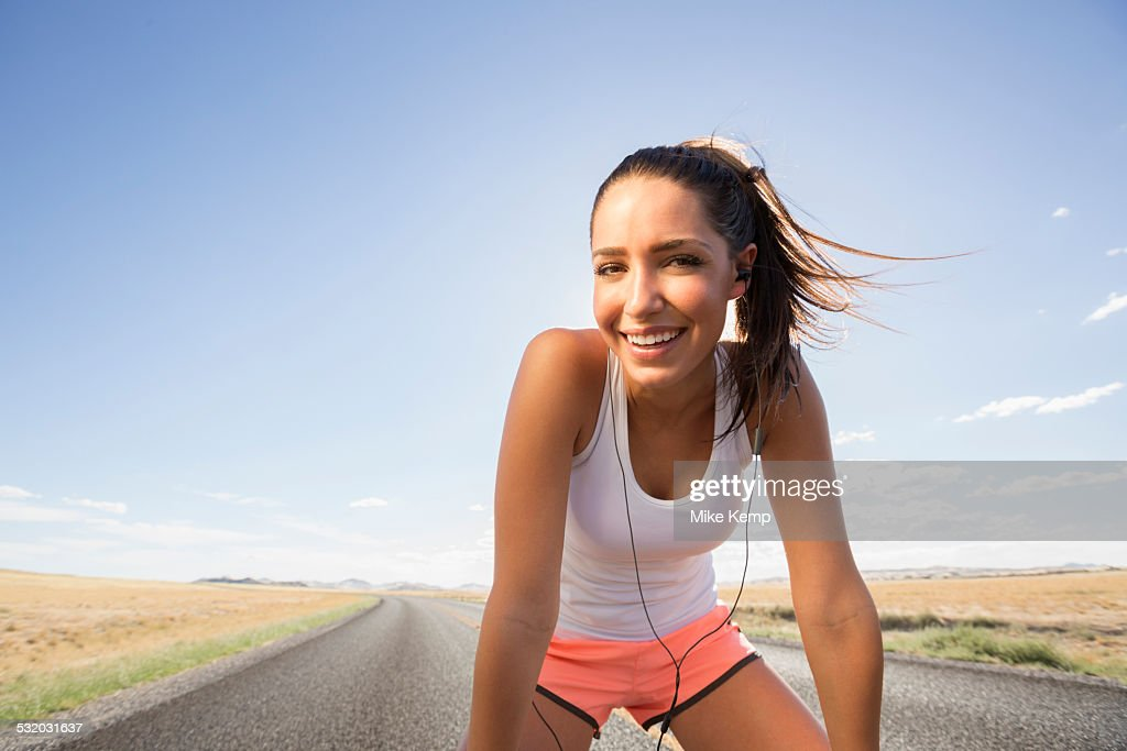 Caucasian runner resting on remoter road : Stock Photo