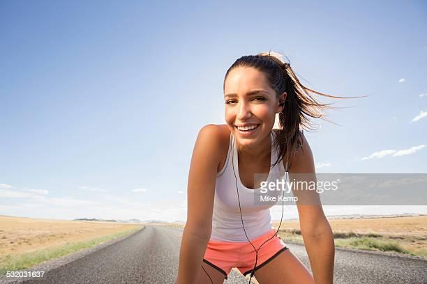 Caucasian runner resting on remoter road