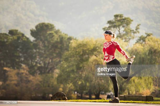 caucasian runner stretching in park - standing on one leg stock pictures, royalty-free photos & images