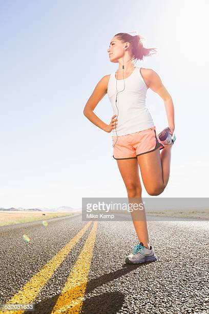 Caucasian runner stretching on remote road