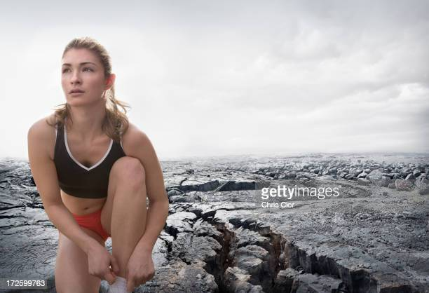 caucasian runner tying shoes on rock formation - lace fastener stock pictures, royalty-free photos & images