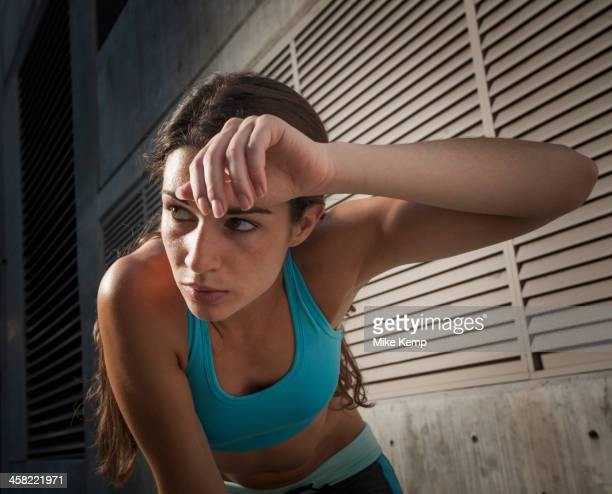 Caucasian runner wiping sweat off forehead