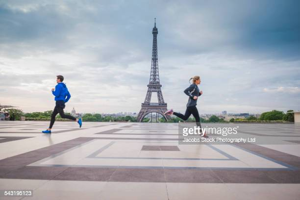 Caucasian runners jogging near Eiffel Tower, Paris, France