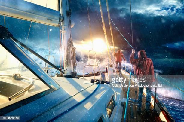 Caucasian sailors on yacht in stormy seas