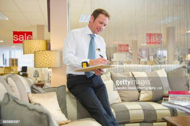 Caucasian salesman checking inventory in furniture store
