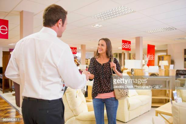 caucasian salesman greeting customer in furniture store - deal england stock photos and pictures