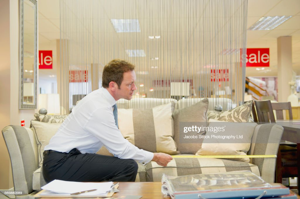 Caucasian Salesman Measuring Furniture In Store : Stock Photo