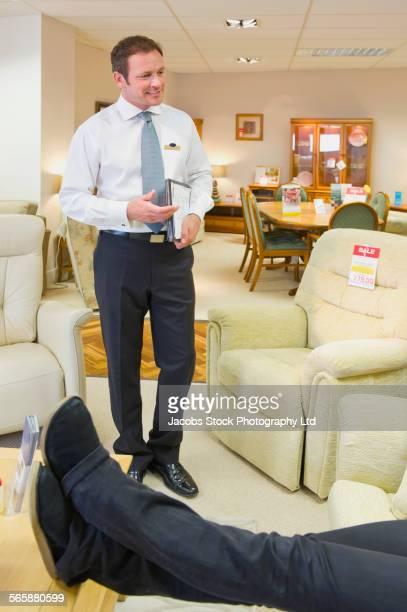 Caucasian salesman talking to customer in furniture store