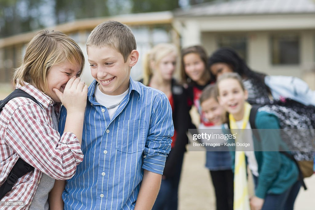 Caucasian school boys whispering together : Stock Photo