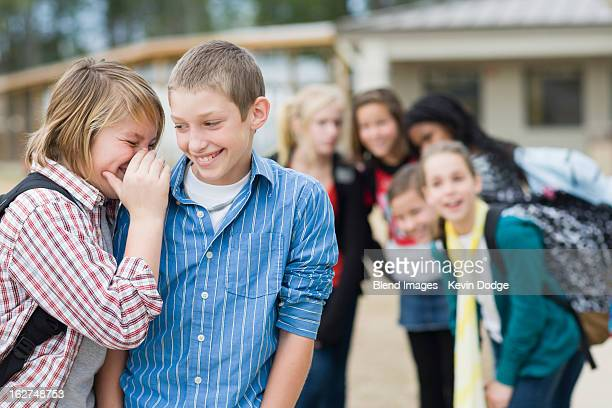 caucasian school boys whispering together - teasing stock pictures, royalty-free photos & images