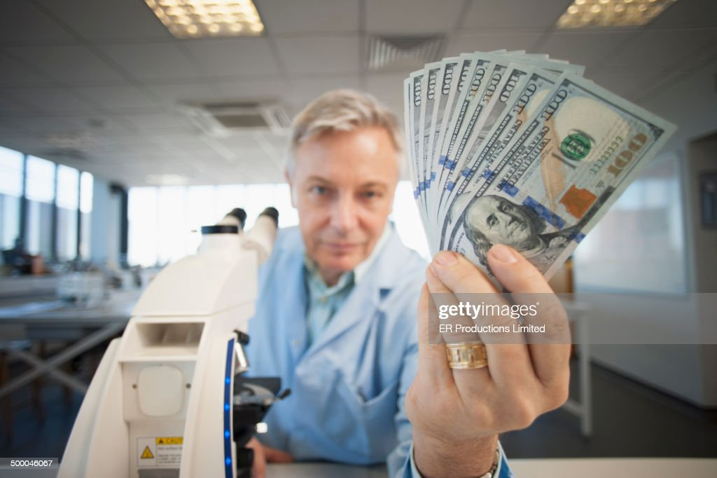 Caucasian scientist holding wad of money in lab : Stock Photo