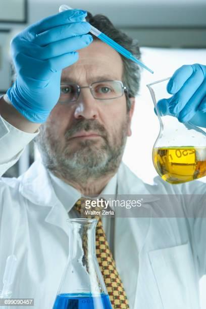 Caucasian scientist mixing liquid in laboratory