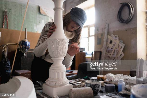 Caucasian sculptor carving plaster piece
