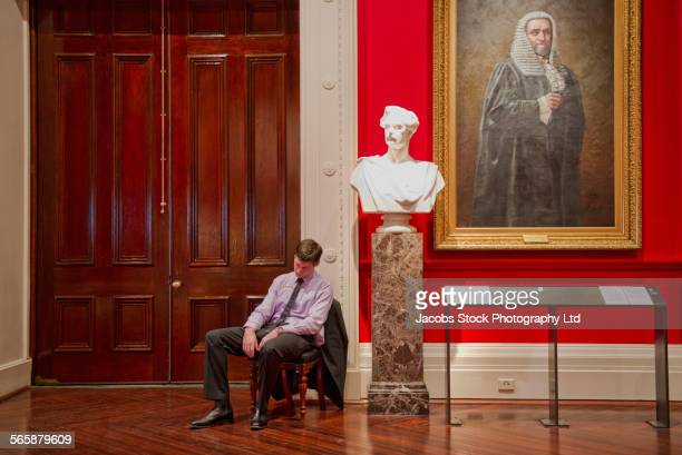 Caucasian security guard napping in art museum