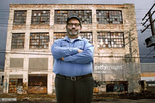caucasian security guard outside dilapidated building - detroit michigan stock-fotos und bilder