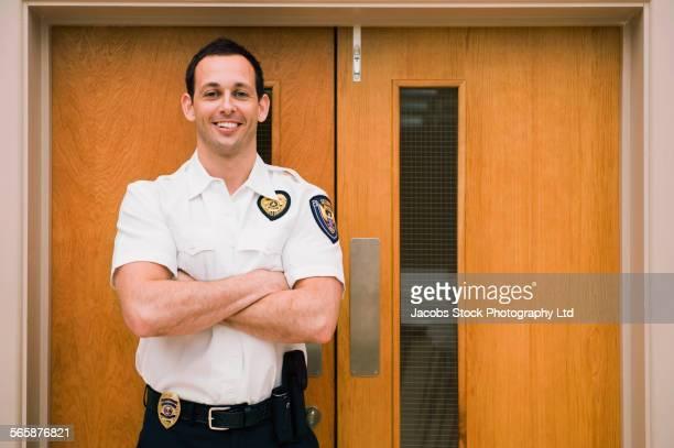 Caucasian security guard standing at door