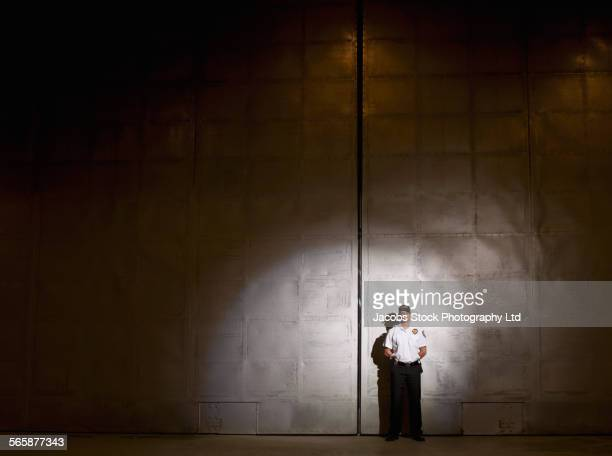 caucasian security guard standing at warehouse doors - guarding stock photos and pictures