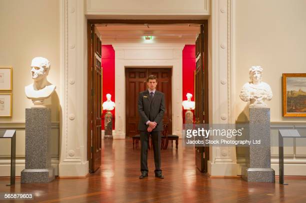 Caucasian security guard standing in art museum