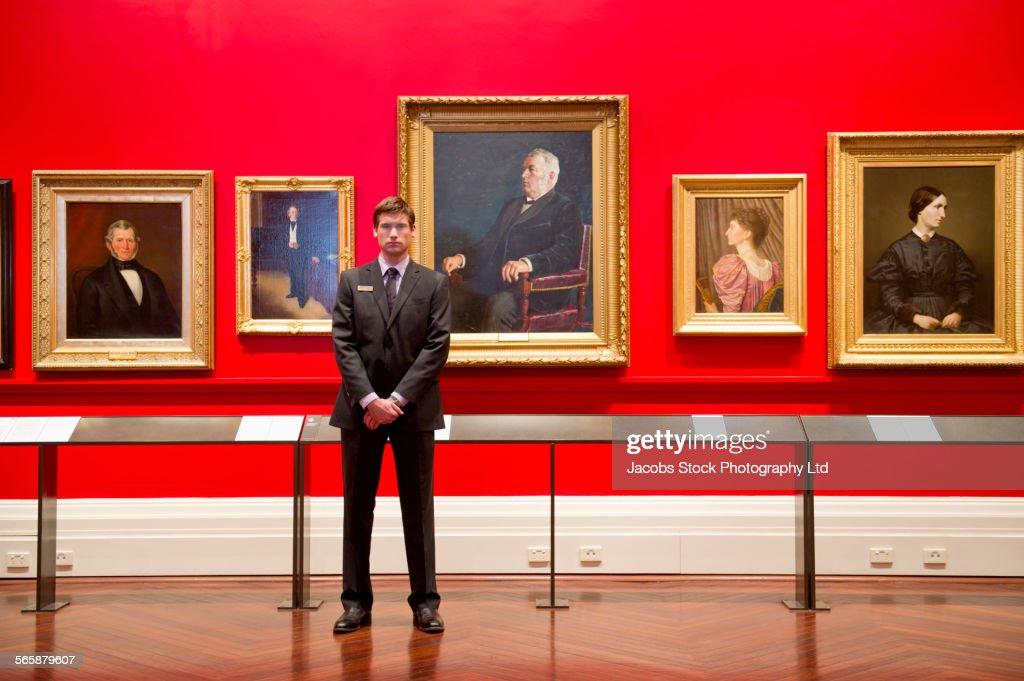 Caucasian security guard standing in art museum : Stock-Foto