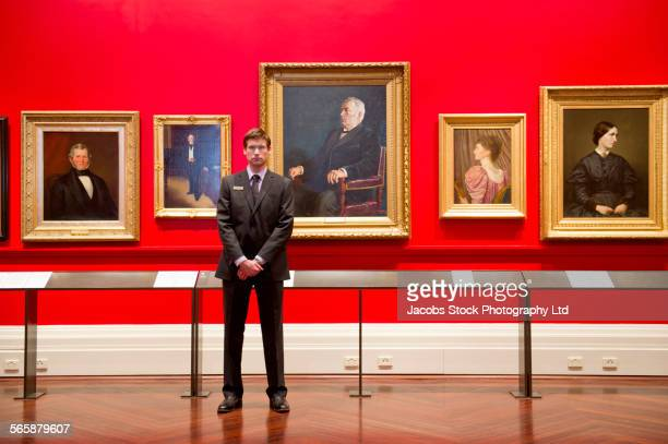 caucasian security guard standing in art museum - guarding stock photos and pictures