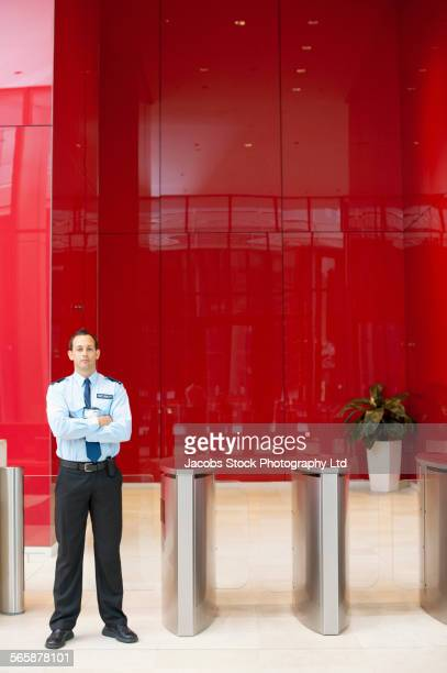 Caucasian security guard standing in lobby near turnstiles