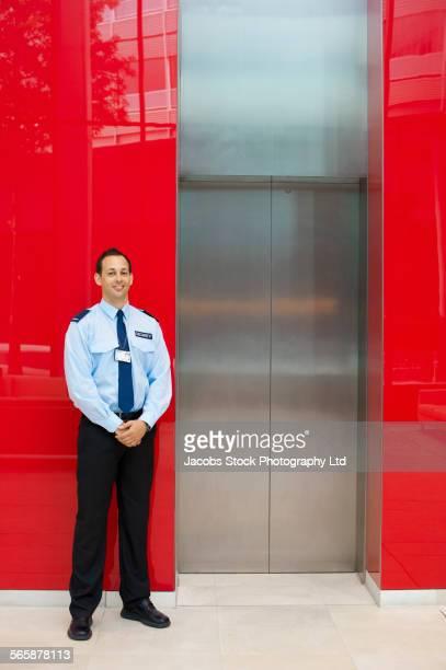 Caucasian security guard standing near office elevator