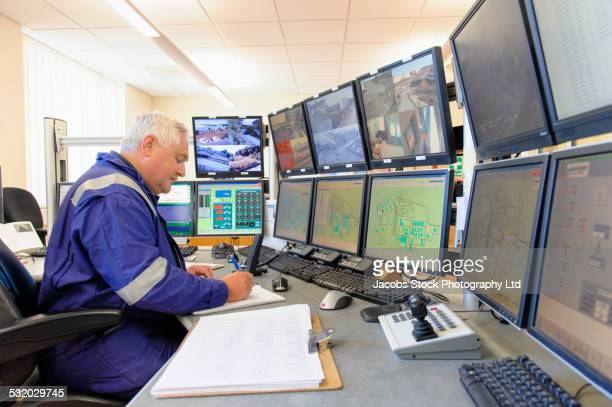 Caucasian security officer monitoring screens in control center