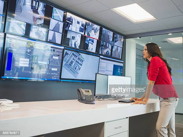 Caucasian security officer watching surveillance cameras