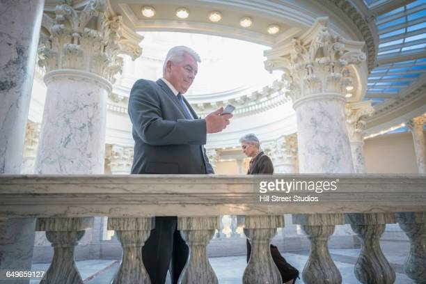 Caucasian senator using cell phone in capitol