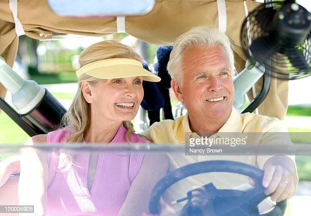 Caucasian senior couple in golf cart.