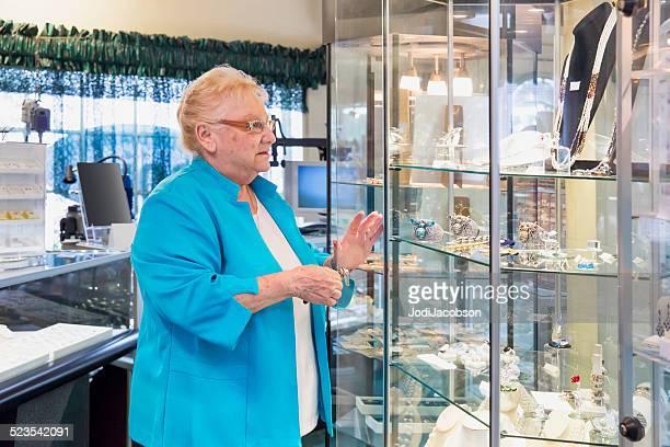 mujer caucásica senior joyería propietario de bloqueo de una carcasa de display - jeweller fotografías e imágenes de stock