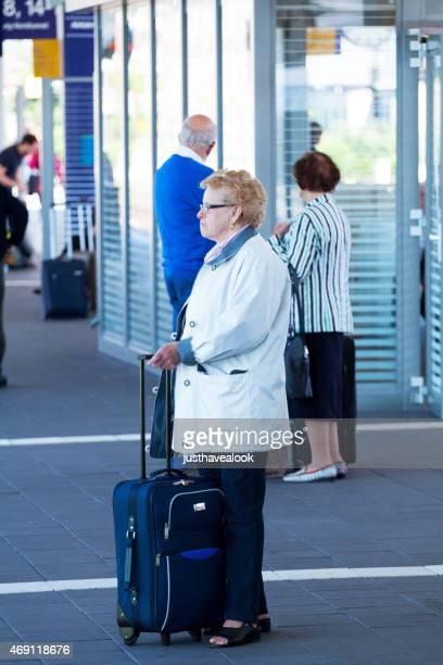 Caucasica senior donna con la valigia in stazione Münster
