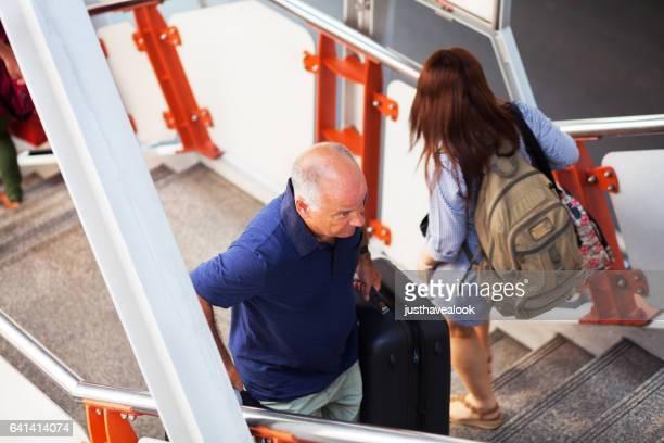 スーツケースは bts に歩いて階段を上ると白人の senuior 男 - senioren männer ストックフォトと画像