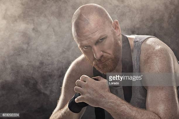 caucasian shaved male adult redhead boxer sitting alone after workout - débardeur photos et images de collection