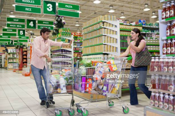 Caucasian shoppers crashing into each other at grocery store