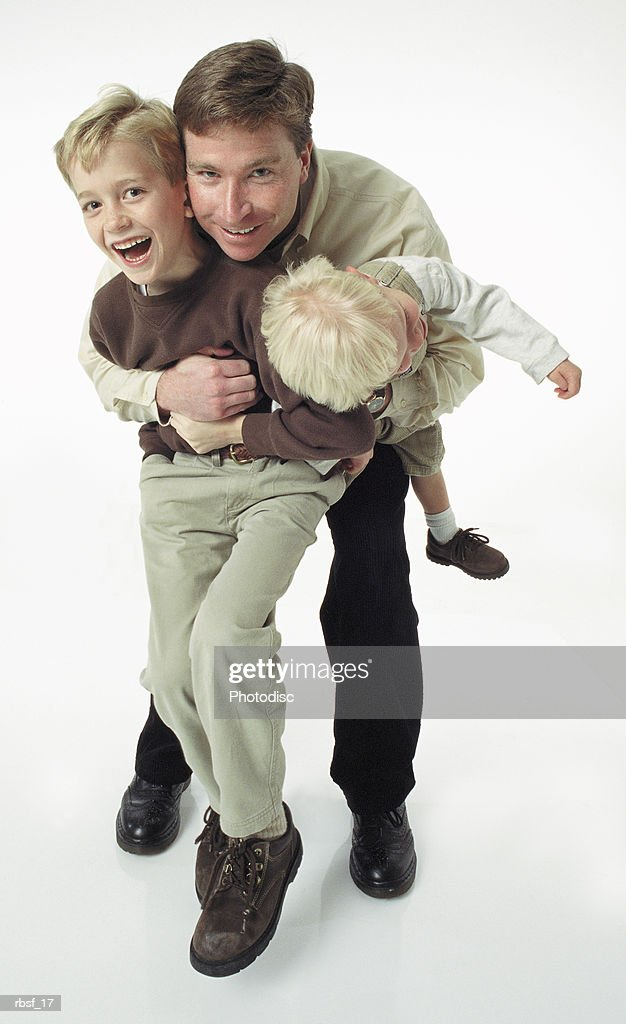 caucasian single father plays with two laughing blonde boys : Foto de stock