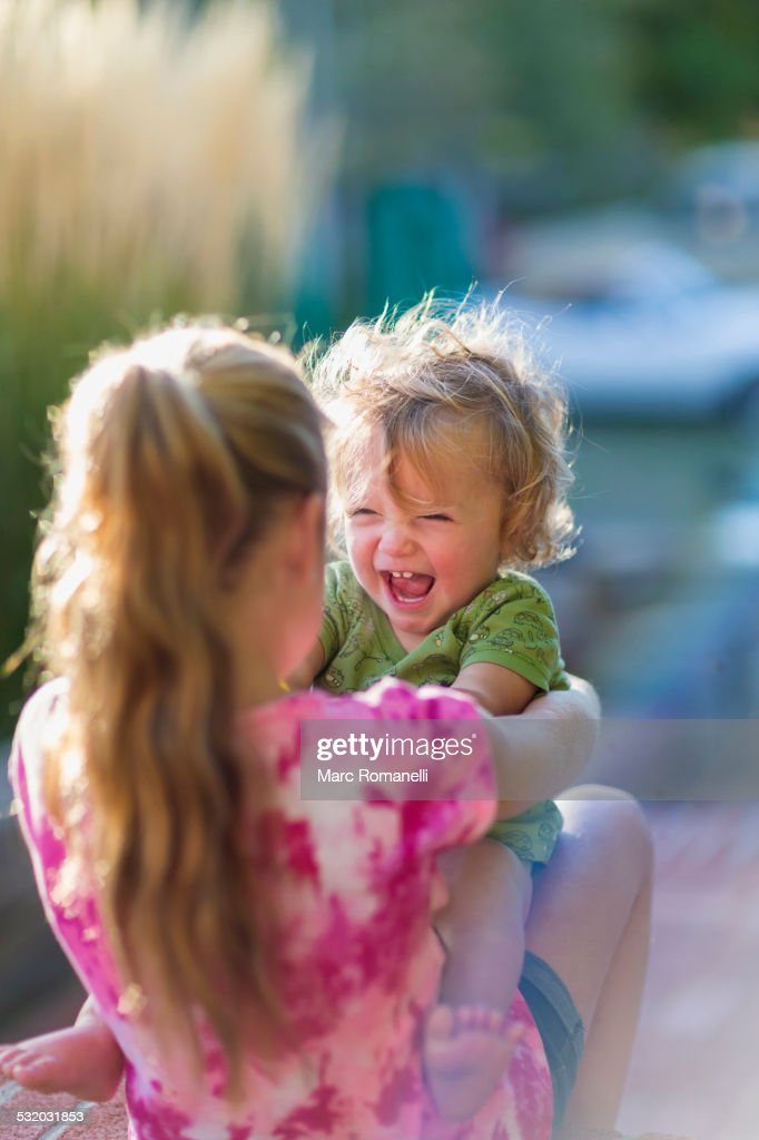 Caucasian sister holding laughing baby brother outdoors : Stock Photo