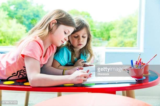 Caucasian sisters drawing at table in playroom