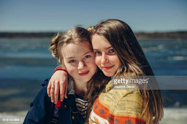 caucasian sisters hugging on beach - teen russia stock photos and pictures