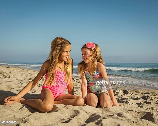 caucasian sisters smiling on beach - 6 7 jaar stockfoto's en -beelden
