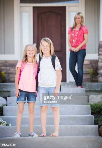 Caucasian sisters smiling on front steps on way to school